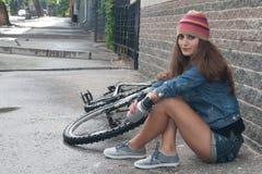 NIZHNIY NOVGOROD, RUSSIA - JULY 21, 2012: Girl wearing knit with denim jacket and shorts sitting with her bicycle at wall. NIZHNIY NOVGOROD, RUSSIA - JULY 21 stock photo