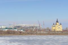 Nizhny Novgorod, Rusia - 14 de marzo 2017 La catedral de Alexander Nevsky y la construcción de un estadio de fútbol Imágenes de archivo libres de regalías