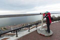 Nizhny Novgorod, Rusia - 11 de noviembre de 2015 El muchacho mira a través de los prismáticos en el río Volga del puesto de obser Fotos de archivo libres de regalías