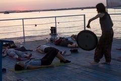 Nizhny Novgorod, Russia, August 18, 2016: yoga on the pier at sunset. Nizhny Novgorod, Russia, August 18, 2016: the instructor beats the gong during meditation royalty free stock photos