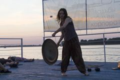 Nizhny Novgorod, Russia, August 18, 2016: yoga on the pier at sunset. Nizhny Novgorod, Russia, August 18, 2016: the instructor beats the gong during meditation royalty free stock photography