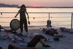 Nizhny Novgorod, Russia, August 18, 2016: yoga on the pier at sunset. Nizhny Novgorod, Russia, August 18, 2016: the instructor beats the gong during meditation royalty free stock image