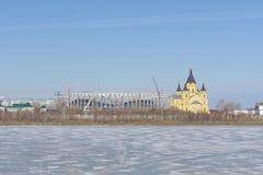Nizhny Novgorod russia - Mars 14 2017 Domkyrkan av Alexander Nevsky och konstruktionen av en fotbollsarena Royaltyfria Bilder
