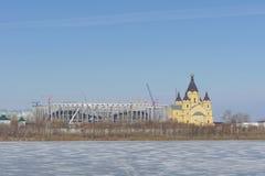 Nizhny Novgorod russia - Mars 14 2017 Domkyrkan av Alexander Nevsky och konstruktionen av en fotbollsarena Arkivfoton