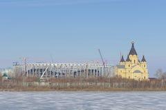 Nizhny Novgorod russia - Mars 14 2017 Domkyrkan av Alexander Nevsky och konstruktionen av en fotbollsarena Fotografering för Bildbyråer