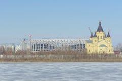 Nizhny Novgorod russia - Mars 14 2017 Domkyrkan av Alexander Nevsky och konstruktionen av en fotbollsarena Royaltyfri Fotografi