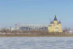 Nizhny Novgorod russia - Mars 14 2017 Domkyrkan av Alexander Nevsky och konstruktionen av en fotbollsarena Arkivfoto