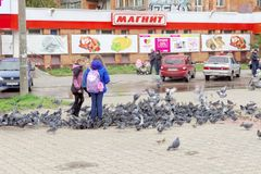 Nizhny Novgorod, Russia. - October 06.2017. Children teens feed a large flock of pigeons on the prospectus of the 70th anniversary Royalty Free Stock Image
