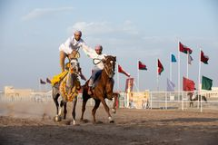 Omani men showing off their riding skills. Royalty Free Stock Images