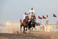 Omani men showing off their riding skills. Royalty Free Stock Photography
