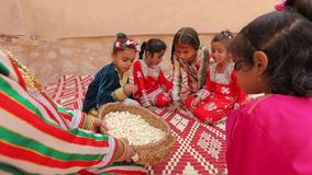 Arab girls in traditional oriental clothes celebrate the holiday with sweets. Nizwa, Oman, - February 2019. Arab girls in colorful traditional oriental clothes stock video
