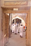 NIZWA, OMAN - FEBRUARY 3, 2012: Entrance of the East Souq in Nizwa Old Town with Omani men traditionally dressed Royalty Free Stock Photo