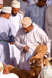 NIZWA, OMAN - FEBRUARY 3, 2012: Omani men traditionally dressed attending the Goat Market in Nizwa Royalty Free Stock Images
