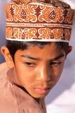 NIZWA, OMAN - FEBRUARY 3, 2012: Portrait of a little Omani boy traditionally dressed attending the Goat Market. Portrait of a little Omani boy traditionally Stock Photo