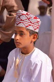 NIZWA, OMAN - FEBRUARY 3, 2012: Portrait of a little Omani boy traditionally dressed attending the Goat Market in Nizwa Stock Photo