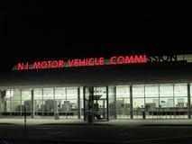 NJ αναμμένο η Επιτροπή σημάδι μηχανοκίνητων οχημάτων με μερικές επιστολές αναμμένες τη νύχτα σε NJ Ð « Στοκ Φωτογραφίες