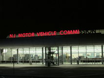 DMV. NJ Motor Vehicle Commission lighted sign with some letters not lighted at night in NJ. Г. Kneeling employee cleaning entrance floor. Bright sign on the Stock Photos