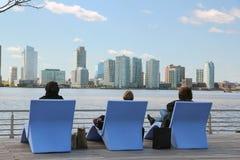 NJ skyline. Three women sitting on the boardwalk Royalty Free Stock Image