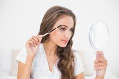 Nöjd attraktiv brunett genom att använda en ögonbrynborste och spegel Royaltyfri Bild