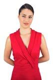 Nöjd sexig brunett i rött posera för klänning Arkivbilder