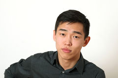 Nöjd ung asiatisk man som ser kameran Royaltyfria Foton