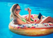 Njoying-Sonnenbräune Frau im Bikini auf der aufblasbaren Matratze im Swimmingpool unter Verwendung der digitalen Tablette und der stockbild
