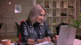 Njutbar framsida av den caucasian blonda flickan som lyckligt ser, och kyla på skärmen av hennes dator och proudly nickar stund arkivfilmer