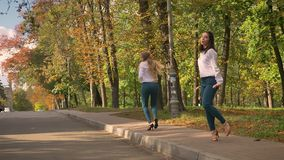 Njutbara Caucasian blondin- och brunettkvinnlig dansar Jive Synchronically på vandringsledet, Green Park bakom som är solig arkivfilmer