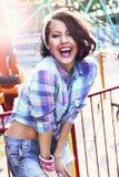 Njutning. Glädje. Uttrycksfull kvinna i rutig skjorta med Toothy leende Fotografering för Bildbyråer