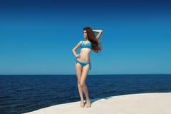 njutning Kvinna för modemodell i bikini över blå himmel, utomhus Royaltyfri Fotografi