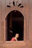 NLE, МЬЯНМА 24-ое ноября: Молодой монах послушника на окне деревянном Chu Стоковые Изображения RF