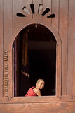 NLE,MYANMAR-November 24 : Young novice monk at window wooden Chu Royalty Free Stock Images