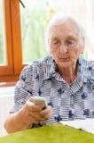 Número discado da mulher superior no telefone celular Fotos de Stock
