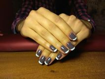The manicurist excellently made her work a beautiful manicure with a polish gel on her hands and the client is happy Stock Photography