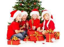 Noël badine dans le chapeau de Santa avec des figts de présents se reposant sous le tre de sapin Image stock