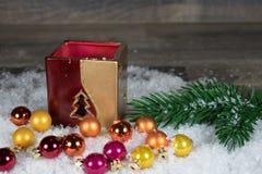 Noël, bougeoirs avec les boules colorées dans la neige image libre de droits