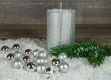 Noël, bougie argentée dans la neige avec des boules de Noël images stock