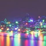 Noël a brouillé des lumières sur le fond noir avec l'espace de copie Réflexions colorées abstraites des ampoules sur un arbre de  Image stock