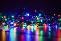 Noël a brouillé des lumières sur le fond noir avec l'espace de copie Réflexions colorées abstraites des ampoules sur un arbre de  Images stock