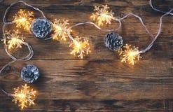 Noël, carte de voeux de nouvelle année, cônes de sapin, lumière de guirlande Images stock