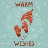 Noël chaud souhaite la carte avec les mitaines et le chapeau confortables Images stock