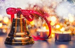 Noël Cloche de Noël avec les bougies rouges de ruban et le fond neigeux Texte de Noël heureux Image stock
