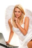 Noël d'ange souhaite prendre avec un ordinateur portatif. Photographie stock libre de droits