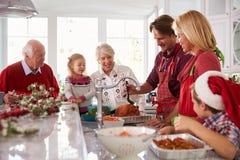 Noël de arrosage Turquie de groupe de famille étendu dans la cuisine photo libre de droits