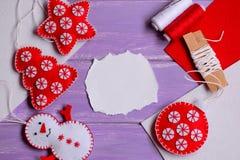 Noël de feutre ouvre des modèles Étoile de feutre, arbre de Noël, bonhomme de neige et boule sur un fond en bois pourpre avec l'e Photo stock