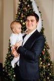 Noël de jeu de père et d'enfant Le papa tient un garçon dans des ses bras dans des glisseurs blancs Père d'affaires Image libre de droits