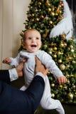 Noël de jeu de père et d'enfant Le papa tient un garçon dans des ses bras dans des glisseurs blancs Père d'affaires Photos libres de droits