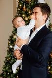 Noël de jeu de père et d'enfant Le papa tient un garçon dans des ses bras dans des glisseurs blancs Père d'affaires Image stock