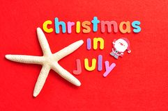 Noël de mots en juillet dans les lettres colorées avec une étoile de mer et une figurine de Santa Photographie stock