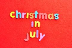 Noël de mots en juillet sur un fond rouge Photos stock